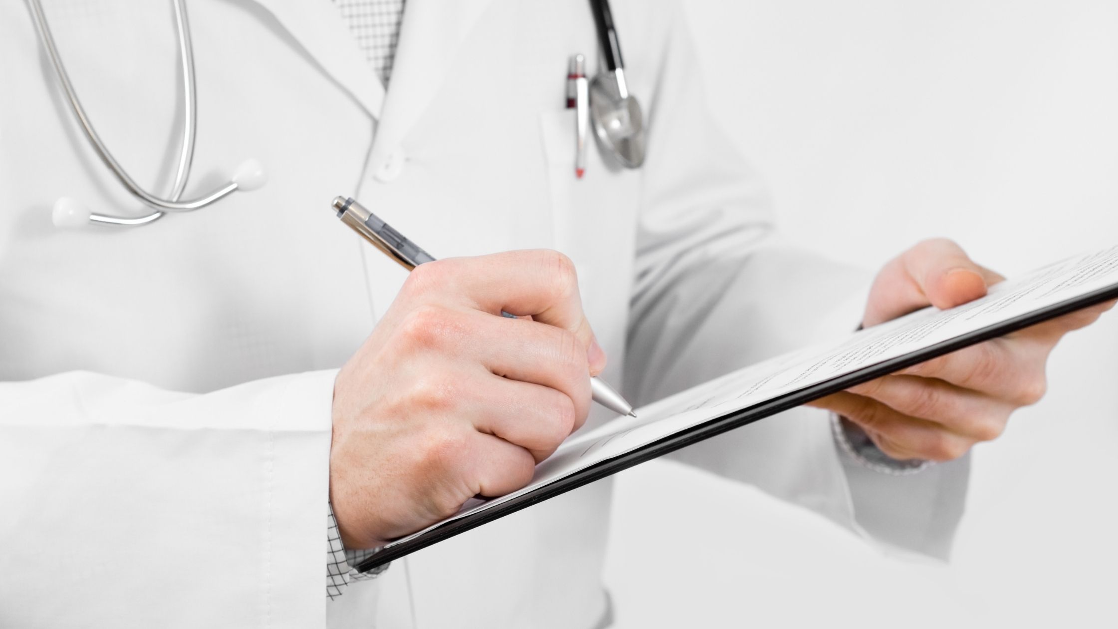 A closeup of a doctor writing on a clipboard
