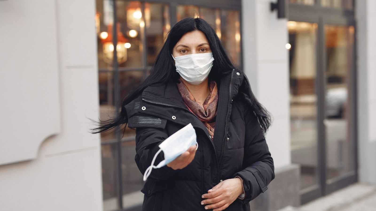 Woman in mask hands out a mask